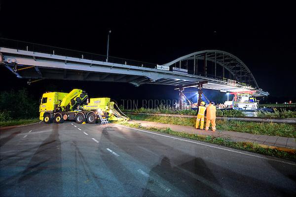 WEESP - In het holst van de nacht wordt door transportspecialist Ale uit Breda, de door ingenieursbureau Movares ontworpen en door bouwcombinatie KWS-Mercon gebouwde stalen Weesperbrug in een kwarter dwars op het Amsterdam-Kanaal gelegd om tussen de landhoofden van de oude Weesperbrug te leggen. De prefab in Gorinchem opgebouwde stalen boogbrug, is één van de vijf nieuwe bruggen die in opdracht van Rijkswaterstaat's project Kargo gebouwd worden, ter vervanging van verouderde bruggen en ter verhoging van de doorvaarthoogte voor vierlaagse containerschepen. Om de pontons met brug erop, strak en vast in het water te houden, werden niet alleen duwboten gebruikt maar stonden op elke oever twee zware vrachtwagens met kabels. Het nauwkeurig invaren duurde een half uurtje. COPYRIGHT TON BORSBOOM
