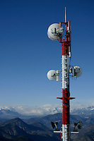 Telecommunication antennas with a view of the French Alps in the background, France.
