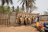 Ghana - Fuveme - Pupils carrying the wall of a private house. Pupils at the Fuvemeh school are often forced to skip class in order to help villagers demolish and move their houses threatened by coastal erosion. During the rainy season, school premises are sometimes used as sleeping places for villagers who lost their houses.