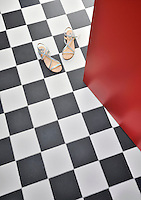 The geometric black and white tiling of a bathroom floor  is offset against the pillar-box red of the door