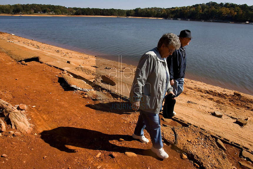 """Lucy and Tolbert Lester walk on the now-exposed grandstands of a submerged race track on Lake Lanier. """"We're just bringing back memories,"""" said Mrs. Lester. The couple frequented the track in the 1950s before the area was flooded. The lake provides water for parts of Georgia, Alabama and Florida."""