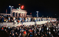The Berlin Wall in front of the Branderburg Gate on the night of November 9th, 1989. Thousands climbed on the Wall as news spread rapidly that the East German Government would now start granting exit visas to anyone who wanted to go to the West. The announcement was misinterpreted as meaning the border was now open and East German border guards were unable to stop the rush of people to the Wall. Within hours people were smashing sections of the Wall with their own hand tools and these first cracks led to the complete opening of the border within days.