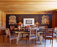 Sculpture, antique books, silverware and a large print add a classical feel to the chalet dining room