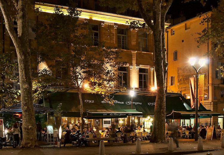 Nighttime shot of Les Deux Garçons, a famous cafe and brasserie on the Cours Mirabeau in Aix-en-Provence, France, that was a favorite of Paul Cézanne, Emile Zola, Pablo Picasso, Marcel Pagnol and other celebrities.