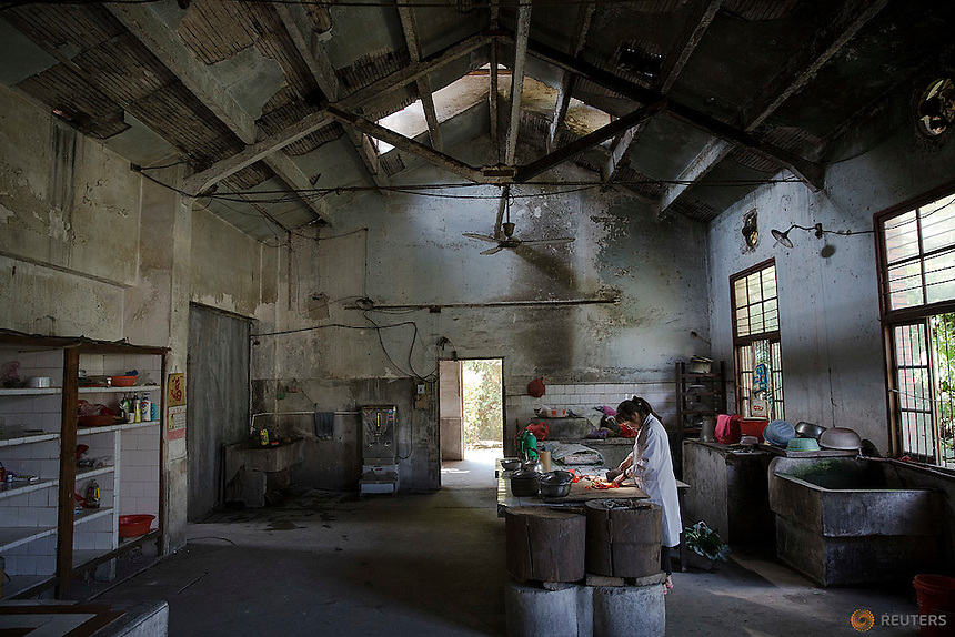 A staff prepares lunch for her colleagues at a dilapidated service building of Yangjia Hospital in Wuji County, China's Zhejiang Province October 19, 2015. Yangjia Hospital, once considered top medical institution treating pneumoconiosis with latest imported equipment is not able to keep the high standards since becoming private in 2001 and is now offering only basic care for remaining patients, all of them former miners suffering from diseases causes by dust in lungs. Patients are often accompanied by their relatives who cook their own food at the hospital.     REUTERS/Damir Sagolj