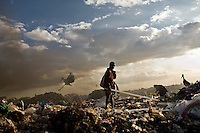 A young boy scavenging florescent light tubes in Kenya's Dandora dump site