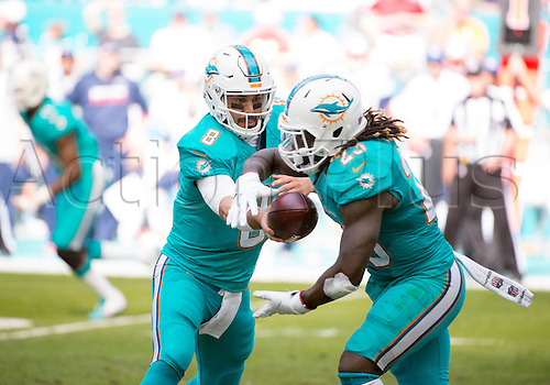 01.01.2017. Miami Gardens, Florida, USA.  Miami Dolphins Quarterback Matt Moore (8) hands off the ball to Miami Dolphins Running Back Jay Ajayi (23) during the NFL football game between the New England Patriots and the Miami Dolphins on January 1st 2017, at the Hard Rock Stadium in Miami Gardens, FL.