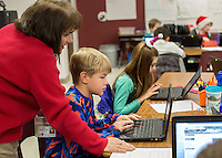 STAFF PHOTO JASON IVESTER --12/18/2014--<br /> Teacher Kim Hamilton helps Stephen Joy (cq), Bellview Elementary fifth-grader, get started with work on a laptop on Thursday, Dec. 18, 2014, in class at the Rogers school.