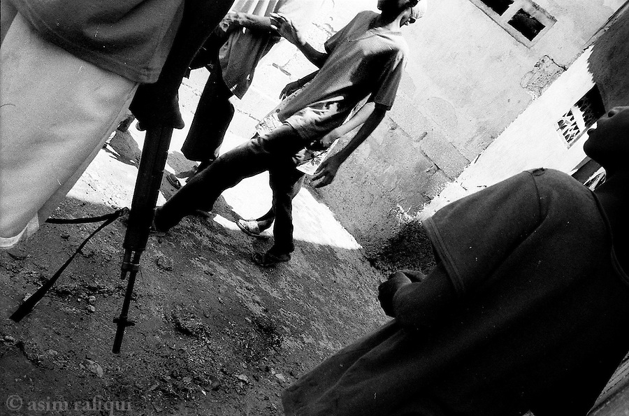 cite soleil, port au prince, haiti, may 2005: boys armed with simple shotguns patrol the streets of cite soleil after the word gets out the there may be a haitian police operation in the area<br />