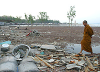 Koh Lanta, Thailand--Esteemed Buddhist monk, Buddha Isara, walks through the remaining debris in the village of Hua Laem on Koh Lanta, Thailand, after the village lost many of its homes and fishing boats to the Tsunami on December 26th, 2004. Isara, who pledged to supply the materials and experienced labor needed to repair the village's fishing boats.  In addition, Isara plans to live in the village for several weeks, primarily to send a message to the Thai government of peaceful resistance to the relocation plans. Within Thailand, Isara is seen as a modern-day Gandhi figure, thus giving the villagers a powerful voice. 01/31/05 © Julia Cumes / The Image Works