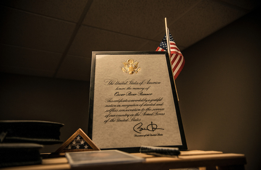 A certificate honoring the military service of Oskar Bear Runner signed by president Barack Obama on the shelf in the shelter for homeless veterans in Pine Ridge Indian Reservation.