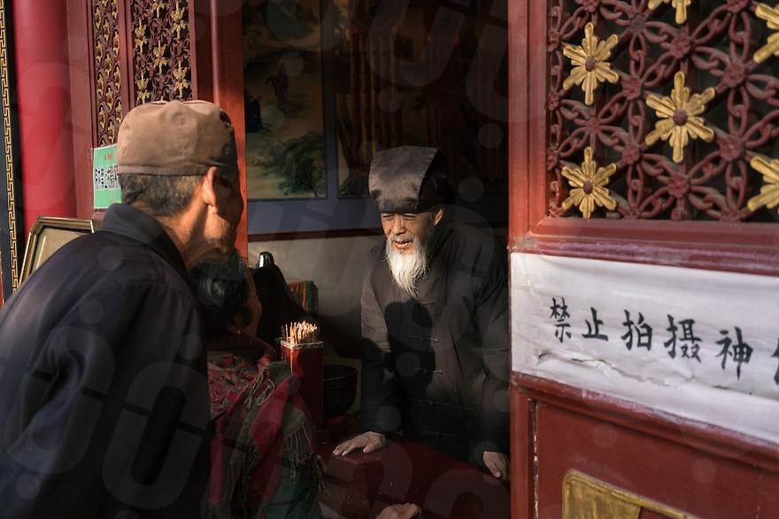 January 12, 2017 - Tayu village, Shaanxi (China). A Taoist monk assists devotees to preparing an offer in one the temple part of the Louguantai's complex. © Thomas Cristofoletti / Ruom for Sixthtone