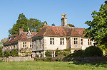 Large detached extended historic farmhouse built from chalk stone in village of Compton Bassett, Wiltshire, England, UK