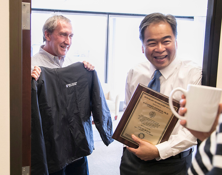 Bob Janis, vice president of facility operations, presents DePaul President A. Gabriel Esteban, Ph.D., a jacket before a tour of the Loop Campus Wednesday, July 5, 2017. Esteban spent an hour getting acquainted with some of the spaces and faces in the Loop during his busy first week on the job. (DePaul University/Jamie Moncrief)