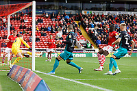 A shot by Bersant Celina of Swansea City (C) is blocked by Brad Collins of Barnsley (L) during the Sky Bet Championship match between Barnsley and Swansea City at Oakwell Stadium, Barnsley, England, UK. Saturday 19 October 2019