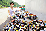 Sonae Fujii of the Zero Waste Academy in Kamikatsu stands next to containers filled with waste ready for recycling at the Hibigaya Waste Station in central Kamikatsu Town in Shikoku, JapaN.