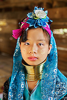 Mae Hon Song, Northern Thailand 2003. Girl from the Padaung tribe. The Padaung-Karen tribes are also known as long neck or giraffe women. Many of the women have been wearing the neck coils since the age of five, which pushes their clavicles downward, giving them the illusion of having a longer neck. There are thought to be about 7000 originally from Burma/Myanmar, although about 500 have fled the civil unrest of their country to live on the Thai border where the women weave handicrafts and the men work in the fields. The Padaung don't receive refugee status by the Thai government and now rely on the generosity of curious tourists.