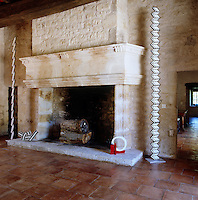 A pair of tall sculptures by Pierre Clerk stand like sentrys either side of the fireplace