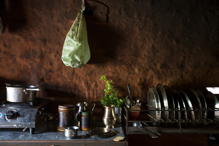 """Nepal - Kathmandu - Kitchen of Sir Kumar Lama, 30, in his house of Mahadevsthan-6, on the outskirts of Kathmandu. The father of a 3-year-old son, Lama has just come back from Qatar, where he spent one year working as a welder in a factory. Rather than the promised around 360 USD per month, Lama was paid only 220 USD. Lama decided to come back to Nepal one year prior of the termination of its contract but is now struggling to repay the 1,200-USD-loan he had taken with his brother in order to go to Qatar. """"Most of my co-workers had been cheated as well"""" he explains. """"Some have been working for eight years now, but are still stuck in Qatar because of their debts""""."""
