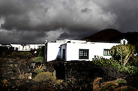 Low angle view of the Cesar Manrique Foundation, Taro de Tahiche, Lanzarote, Canary Islands, Spain, pictured on November 27, 2010 in the afternoon against a cloudy sky. Formerly the artist's studio and home, the house was built in 1968 on the site where a volcano erupted in 1730-36. The living space is formed from five volcanic bubbles and the style is inspired by the traditional local architecture. The Cesar Manrique Foundation, created in 1992, is devoted to the Arts, the Environment, and the conservation, study and promotion of the work of Cesar Manrique. Lanzarote, the Easternmost of the Canary Islands, lies 125km East of the African coast, in the Atlantic Ocean. Like the other islands in this autonomous Spanish archipelago Lanzarote is originally volcanic. Picture by Manuel Cohen.