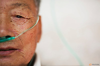 Hu Hushen, a 78 year old former miner breaths using a nasal cannula for oxygen supplement outside his room at Yangjia Hospital in Wuji County, China's Zhejiang Province October 19, 2015. Hu Hushen was diagnosed with pneumoconiosis, a disease caused by dust in lungs in 1976 and stopped working the same year. The former miner decided to move to Yangjia Hospital nine years ago because it's cheap - the oxygen is for free and everything else is almost totally paid by his insurance. Hu lives with constant oxygen supplement for past five years. REUTERS/Damir Sagolj