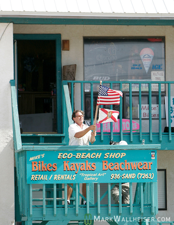 The first Navarre Beach resident allowed back on the island, shop keeper Mike Martino, plants the American and the State flag of Florida at his beach souvenier shop July 11, 2005 after Hurricane Dennis made landfall demolishing the vacation island 10 month after Hurricane Ivan did the same.