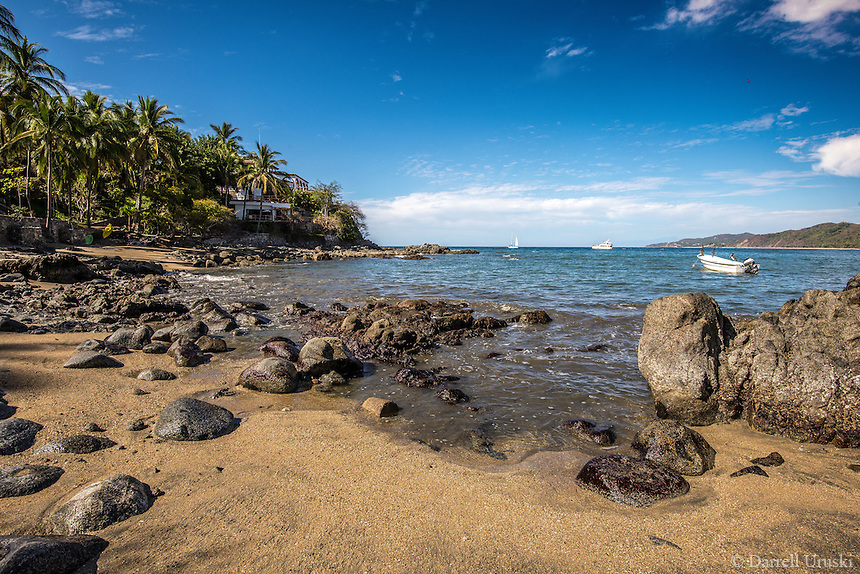 Fine Art Landscape Photograph of the ocean shoreline in Sayulita Mexico. <br /> The sandy beach, the palm trees, and the unique rock formations helped to guide my eyes towards the fishing boats that were floating on the blue ocean of this picturesque tropical scene.