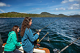 ALASKA, Ketchikan, two women reel in a fish while fishing the Behm Canal near Clarence Straight, Knudsen Cove along the Tongass Narrows