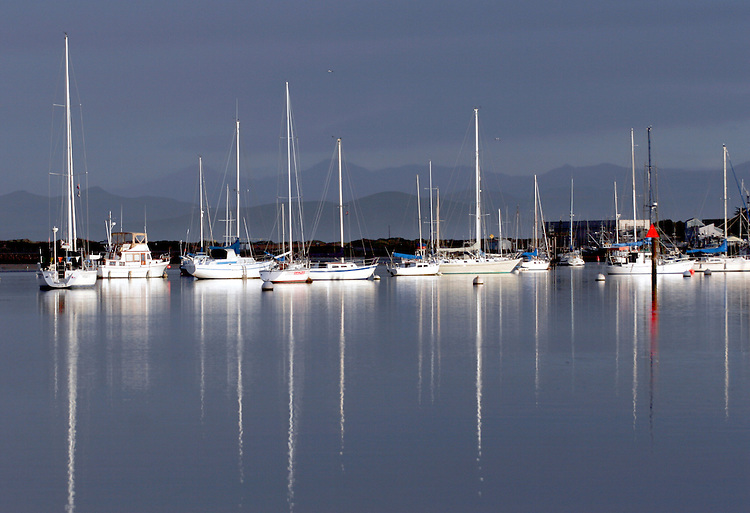 Early morning light highlights anchored sailboats against a stormy sky in Morro Bay on the California central coast.