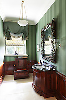A green striped bathroom with polished wood panelling and a grand 'throne' toilet