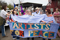 NWA Democrat-Gazette/CHARLIE KAIJO Jules Taylor of Fayetteville (from left), Wendy Love Edge of Fayetteville and Leilani Law of Fayetteville prepare to march during the Parade for Peace, Sunday, March 18, 2018 that started at the Walton Art Center and ended at the Town Center in Fayetteville. <br /><br />&quot;Peace is so much about unity,&quot; said Law. &quot;This is an experiment if we can unify and walk down the street together.&quot;<br /><br />The Arkansas Poor People&acirc;&euro;&trade;s Campaign, the OMNI Center and Arkansas Nonviolence Alliance held a Parade for Peace. The parade featured multiple floats, dancing troops and large art projects.