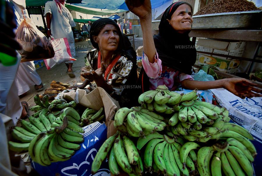 2003. Saudi Arabia. Near the Yemen border. Two women selling bananas in a market place. Arabie Saoudite. Près de la frontière avec le Yemen. Deux femmes vendent des bananes au marché.