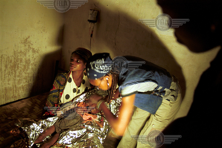 A medical technician examines a child suffering from severe malnurition in the intensive care unit at a MSF theraputic feeding center. The military strategies of the government armed forces and UNITA rebels toward the civilian population has caused widespread devastation and a serious famine situation in the country. Aid organizations have had access to large portions of the country only after a cease fire was signed in April of this year..Bailundo, Angola. 03-08-2002..Photo ©: J.B. Russell / Panos Pictures