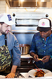 BERMUDA. Hamilton. Hamilton Princess & Beach Club Hotel. Marcus' Restaurant. Chef Marcus Samuelsson and his Executive Chef Leornard Marino talking about a pasta dish in the kitchen.