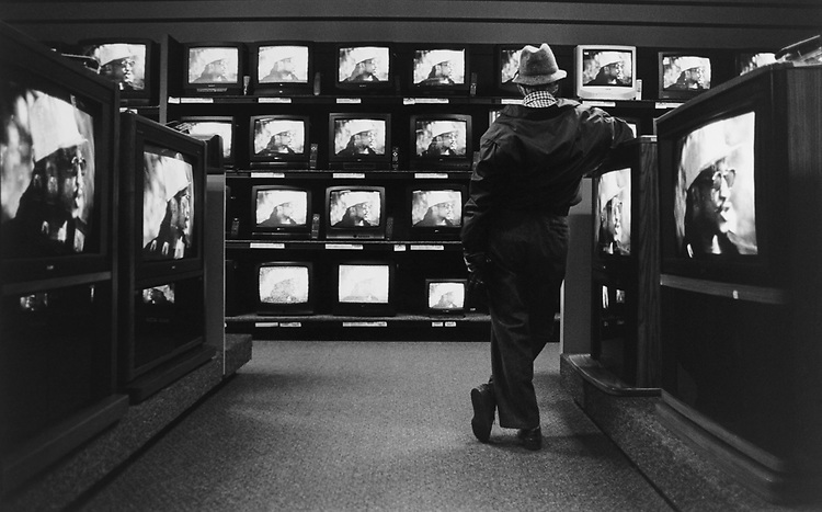 A customer watches tv in tv shop on March 11, 1996. (Photo by Laura Patterson/CQ Roll Call via Getty Images)