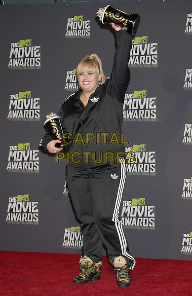Rebel Wilson.2013 MTV Movie Awards held at Sony Pictures Studios, Culver City, California, USA..April 14th, 2013.press room pressroom full  length black adidas tracksuit shell suit trophies award trophy winner hand arm in air.CAP/ADM/RE.© Russ Elliot/AdMedia/Capital Pictures