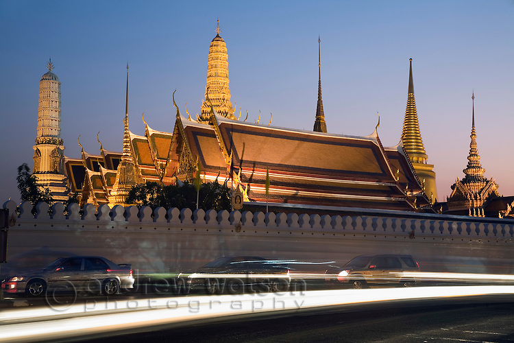Evening traffic passes in front of Wat Phra Kaew and the walls of the Grand Palace.  Bangkok, THAILAND.