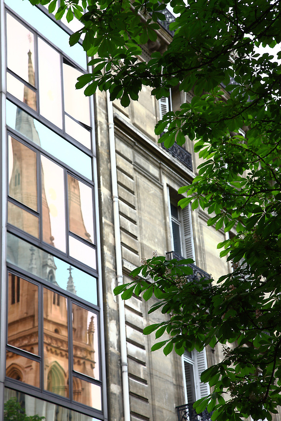 The reflected image of the Saint George's bell tower (it is an Anglican church) onto the glass wall of the modern building in front of it, in Paris. Digitally Improved Photo.