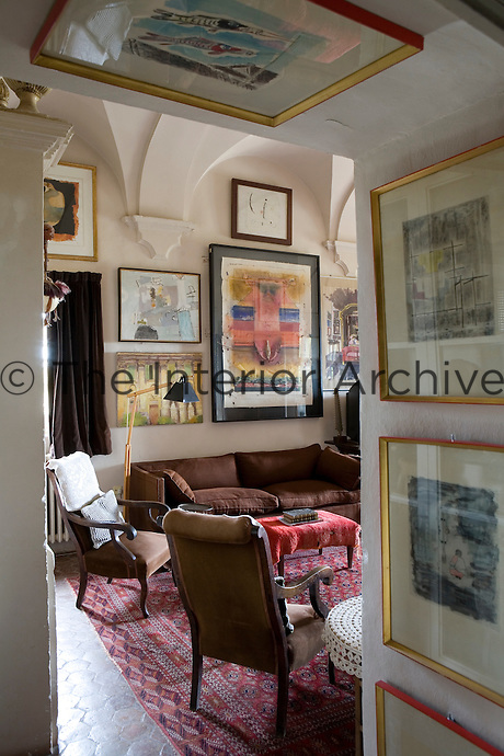 A view into a traditional sitting room furnished with a brown sofa and wooden armchairs. The owner's extensive art collection is displayed on the walls.