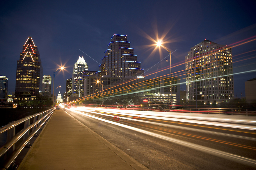 Car lights leave streak trails as they drive down Congress Avenue Bridge with the night time skyline in the background in Austin, Texas.