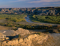 NDTR_113 - USA, North Dakota, Theodore Roosevelt National Park, Evening light on Valley of the Little Missouri River with sedimentary hills rising in the distance, from River Bend Overlook, North Unit.