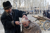 CHINA, province Xinjiang, market day in uighur village Jin Erek near city Kashgar where uyghur people are living, open air barber shop / CHINA Provinz Xinjiang , Markttag in Jin Erek einem uigurischen Dorf bei Stadt Kashgar, hier lebt das Turkvolk der Uiguren , die sich zum Islam bekennen, fliegende Barbiere