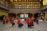 Monks perform a dance in the courtyard of a Monastery in the Paro Valley, Bhutan.