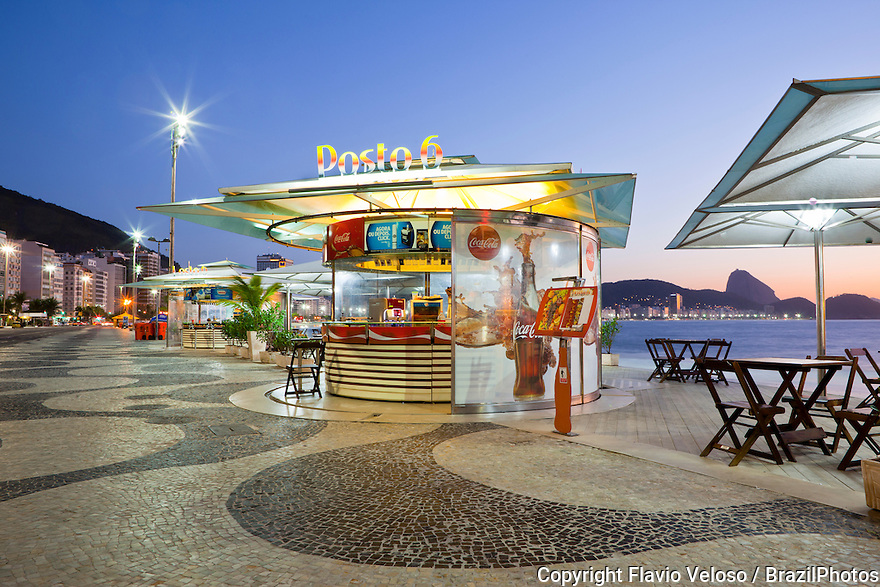 """Stylized and standardized Kiosk named """"Posto 6"""" with restaurant and bar at Copacabana beach sidewalk showing the promenade, a pavement landscape in large scale ( 4 kilometres long ) having a black and white Portuguese pavement design by Roberto Burle Marx, a geometric wave. Sugar Loaf mountain in background at right, Rio de Janeiro, Brazil."""