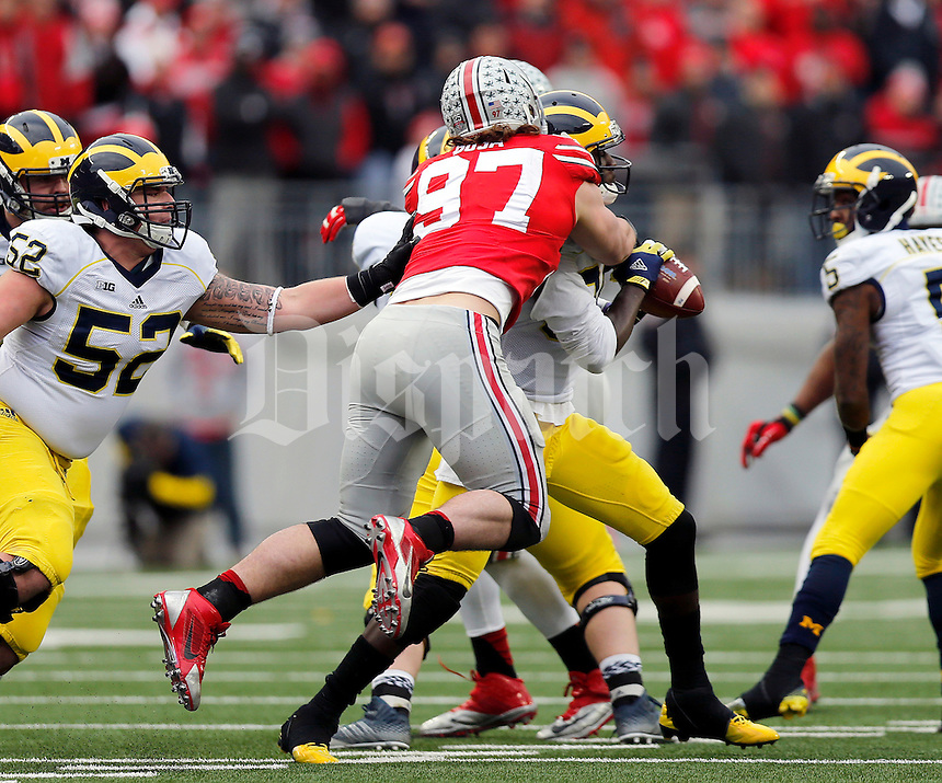 Ohio State Buckeyes defensive lineman Joey Bosa (97) tackles Michigan Wolverines quarterback Devin Gardner (98) during the fourth quarter of the NCAA football game against Michigan at Ohio Stadium on Saturday, November 29, 2014. (Columbus Dispatch photo by Jonathan Quilter)