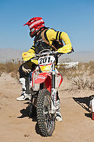 201x motorcycle rider Derek Duncan leaves Honda pit #2 at race mile 70, 2012 San Felipe Baja 250, San Felipe, Baja California, Mexico.