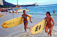 Two teenaged girls run toward the shore at Waikiki Beach, carrying yellow surfboards under their arms. A catamaran and the slope of Diamond Head highlight the background.