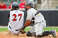 Elias Diaz #30 of the West Virginia Power tags out Kevin Dubler #27 of the Kannapolis Intimidators as he tries to score a run at Fieldcrest Cannon Stadium on April 20, 2011 in Kannapolis, North Carolina.   Photo by Brian Westerholt / Four Seam Images