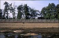 Vermezzo (Milano). Il Naviglio Grande in secca e la strada provinciale --- Vermezzo (Milan). Shallow water in the canal Naviglio Grande and the county road