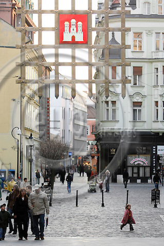 """BRATISLAVA - SLOVAKIA 9. MARCH 2007 -- Street scene from the old city of Bratislava. A girl runs in a pedrestian street of the old city. The weapon of Bratislava is seen on top of the picture -- PHOTO: GORM K. GAARE / EUP & IMAGES..This image is delivered according to terms set out in """"Terms - Prices & Terms"""". (Please see www.eup-images.com for more details)"""